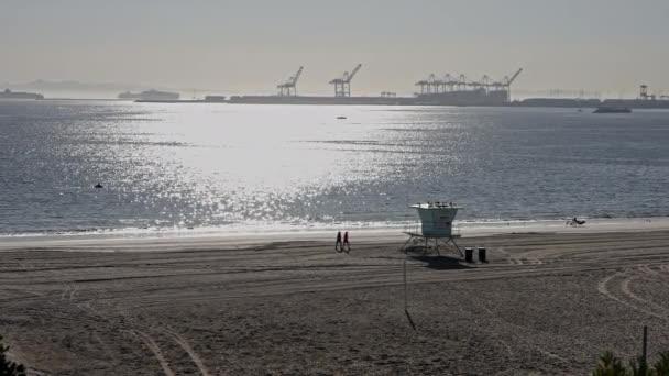 Žena běhá po pláži. Jasnej slunečnej den v Kalifornii. Pohled na nákladní přístav na Long Beach USA. Slunce ozařuje břečťanovou vodu oceánu. Zpomalený pohyb.