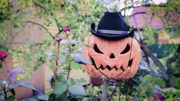 Strašidelná Halloween dýně v kovbojském klobouku v přírodě. Strašák pro letní sídlo se houpe ve větru. 4K