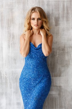Elegant blonde woman in the blue evening sparkling dress is posing near the light texture wall