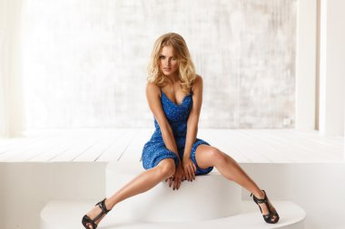 Sexy, sensual and seductive woman in the blue evening sparkling dress with sequins is posing in the light room