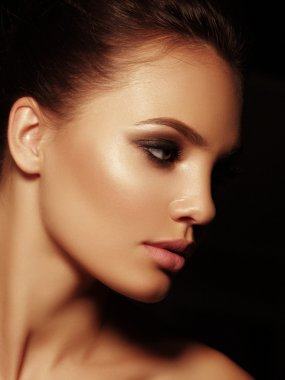 Elegant portrait of a sexy appealing naked brunette with full lips and closed smoky eyes on the black background