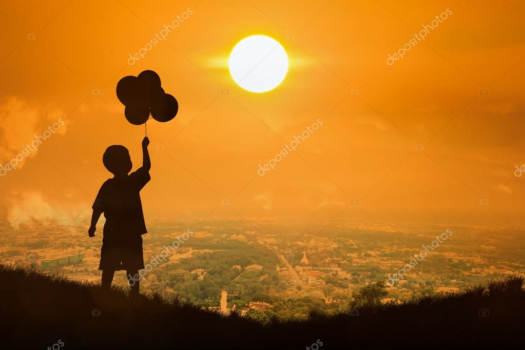 Silhouette of little boy  hold bubble look at  the sun , sunset