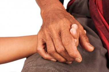 asian kids little boy hand touches and holds an old man wrinkled