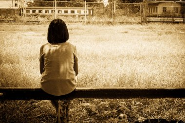 sad asian girl sitting alone  near railway Stations ,vintage ton