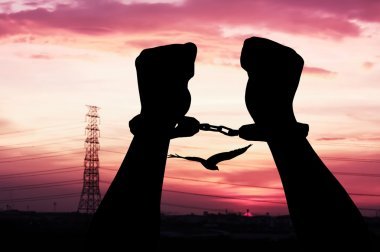 silhouette of hand men in shackle on sunset in city background