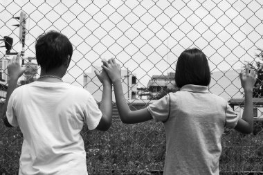 asian little girl sad hand hold jail at Railroad,railway station