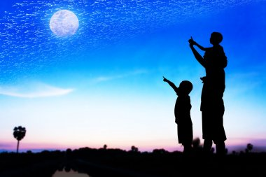 Silhouette of father use hand point his son look at full moon on