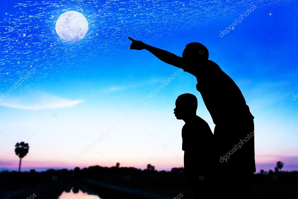 Silhouette of father use hand point his son look at meteor showe
