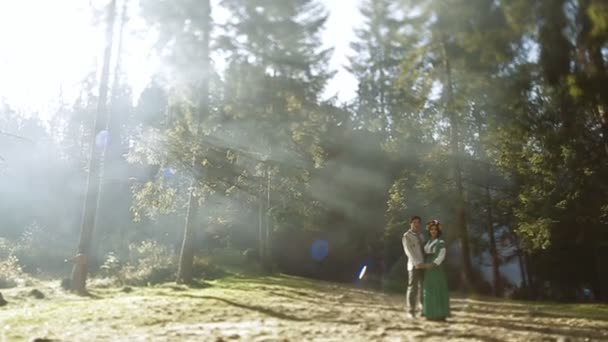 couple in embroidery standing in green forest
