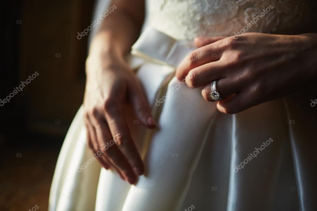 Close up of hands of woman showing the ring with diamond. She is