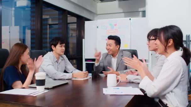 Skupina šťastných asijských podnikatelů diskutovat společně v týmu brainstorm setkání a tleskat ruku, pracovat pozdě v noci v úřadu. Firemní podnikání, týmová práce kolegů nebo koncepce oslavy úspěchu projektu