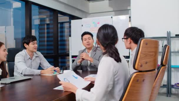 Group of happy Asian business people discuss together in team brainstorm meeting and clap hand, work late night in office. Corporate business, coworker teamwork, or project success celebration concept