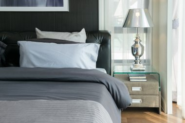 luxury lamp and books on bedside table in bedroom