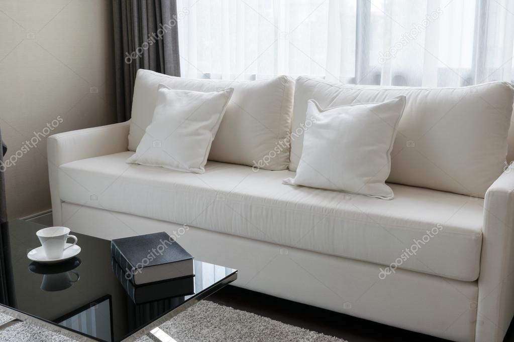 Witte decoratieve kussens op een casual sofa in de woonkamer ...