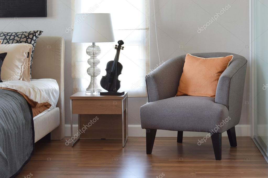 moderne slaapkamer interieur met oranje kussen op grijze stoel en ...