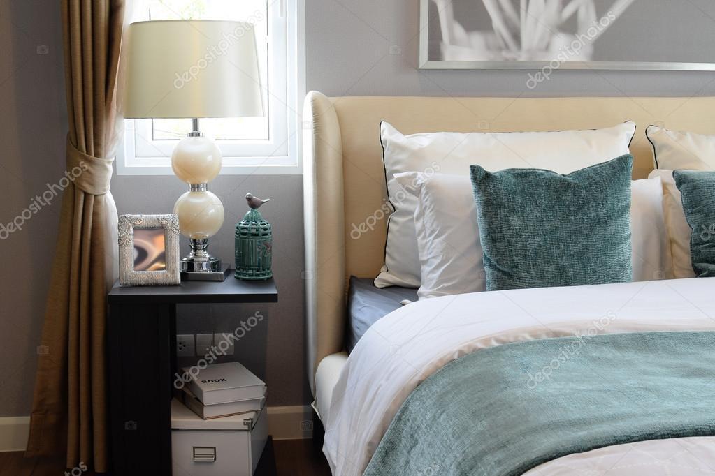 Arredamento camera da letto con cuscini bianchi e verdi sul letto