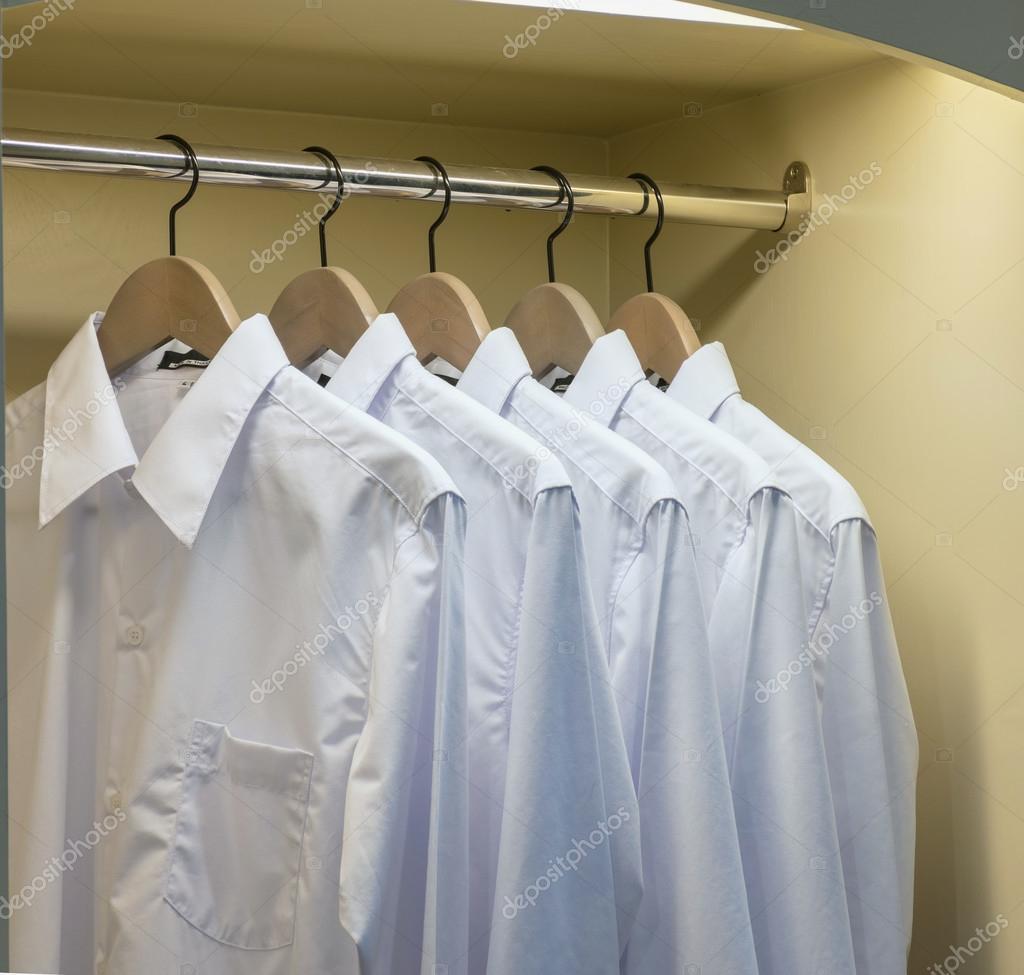 Reihe von weißen Hemden Kleiderbügel im Schrank hängen — Stockfoto ...