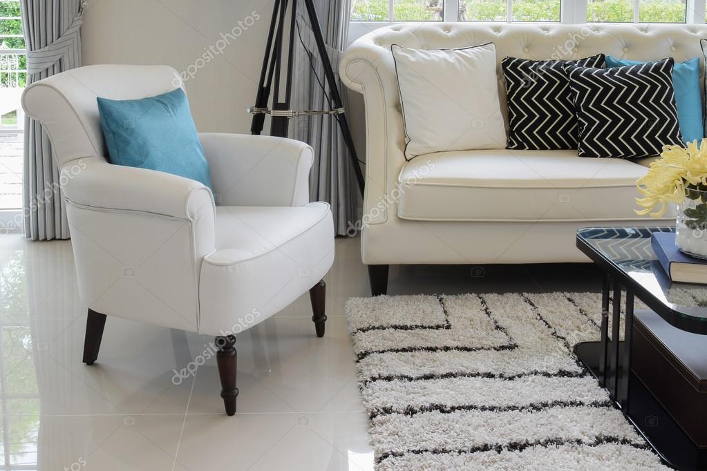 Witte en blauwe kussens op een witte lederen bank in de woonkamer