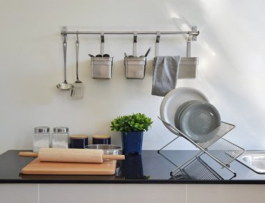modern ceramic kitchenware and utensils on the black granite counter top
