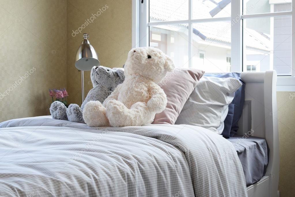 Kinderen kamer met poppen en kussens op bed en nachtkastje