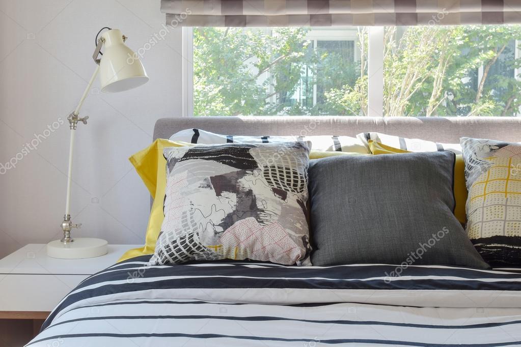 stijlvolle slaapkamer interieur met zwart wit patroon kussens op bed en decoratieve tafellamp stockfoto