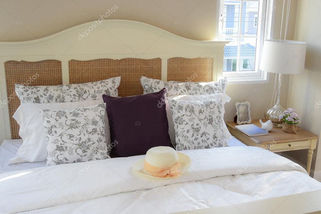 Interno di camera da letto dell\'annata con cuscini di fiori e ...