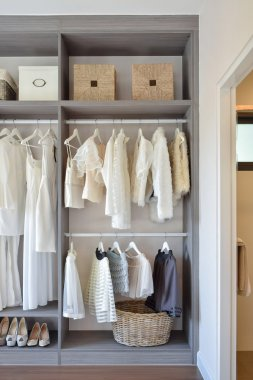modern closet with row of white dress and shoes hanging in wardrobe