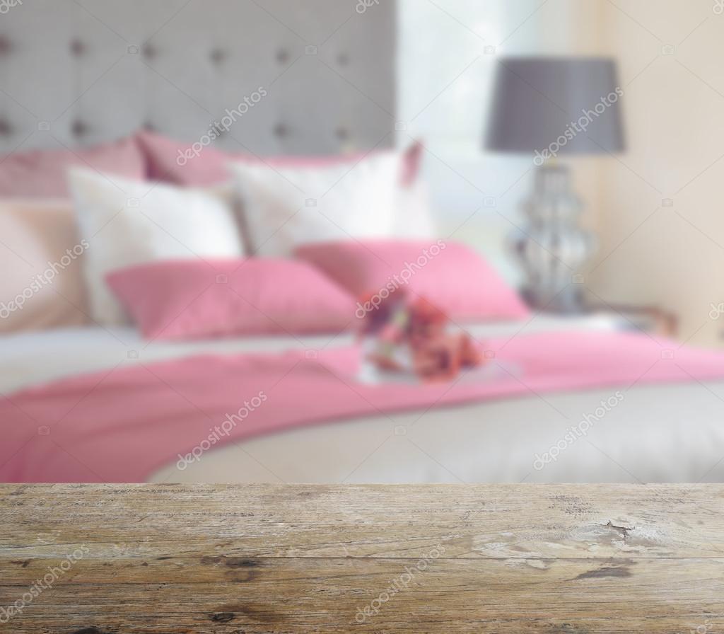 plateau en bois avec le flou de lit rouge et oreillers dans la ...