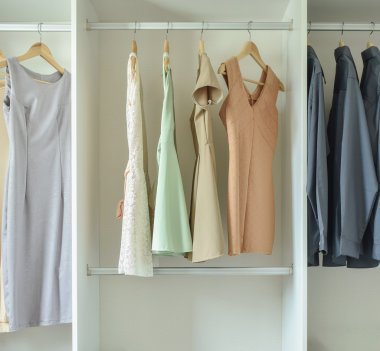 Male and female clothes hanging on hangers in wardrobe