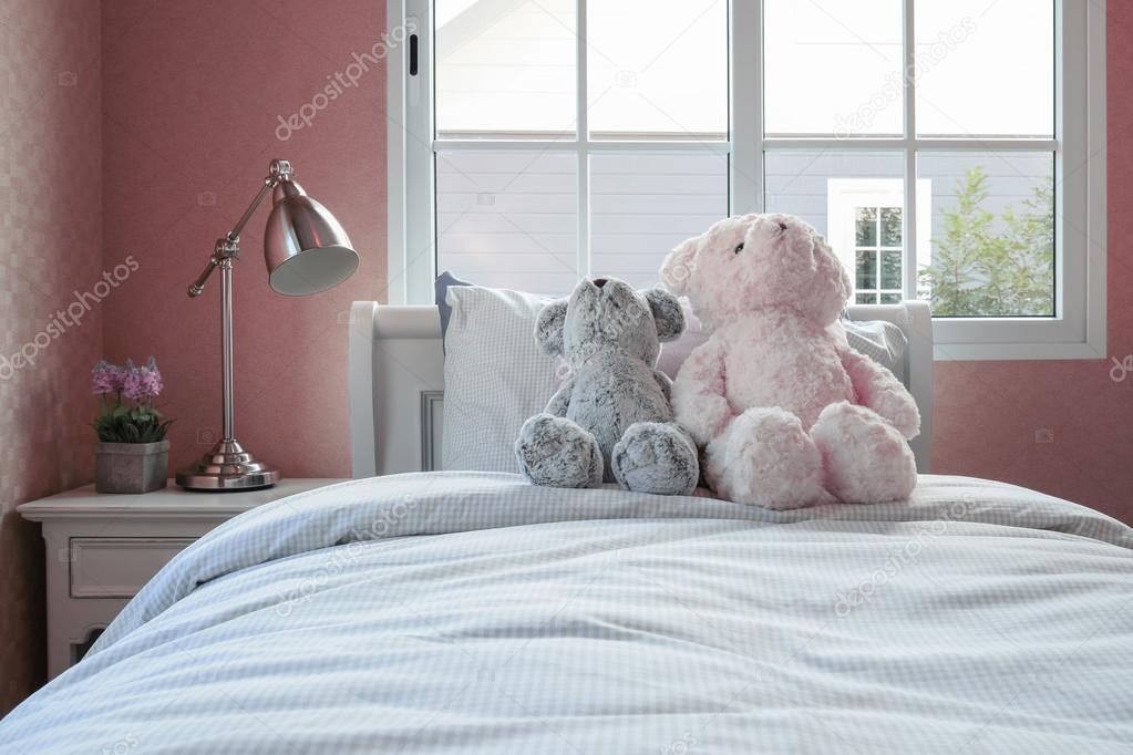 Kinderen kamer met poppen en kussens op bed en nachtkastje tafellamp