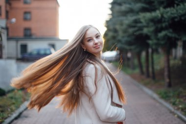 Girl with very long hair standing on the sunset background