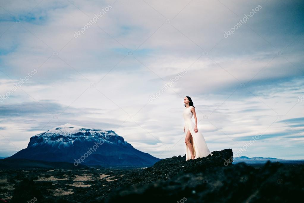 Beautiful young bride near mountain