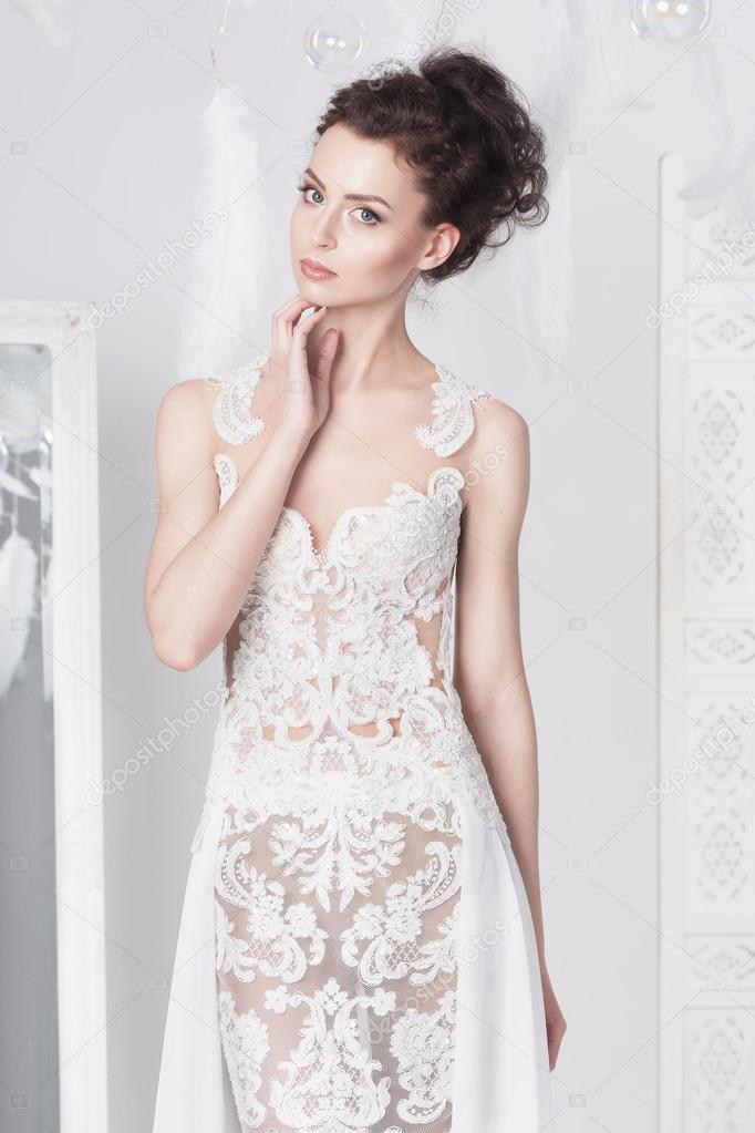 abdd5137a1392a Jonge elegante bruid in een jurk van kant. Ze kijkt recht in de kijker —