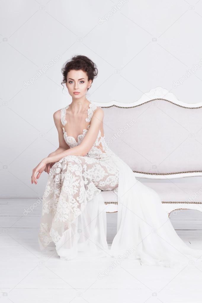 d614551f051068 Mooie jonge bruid in een luxe kant trouwjurk. Ze zit op een witte vintage  sofa. Ze is een elegante en slanke