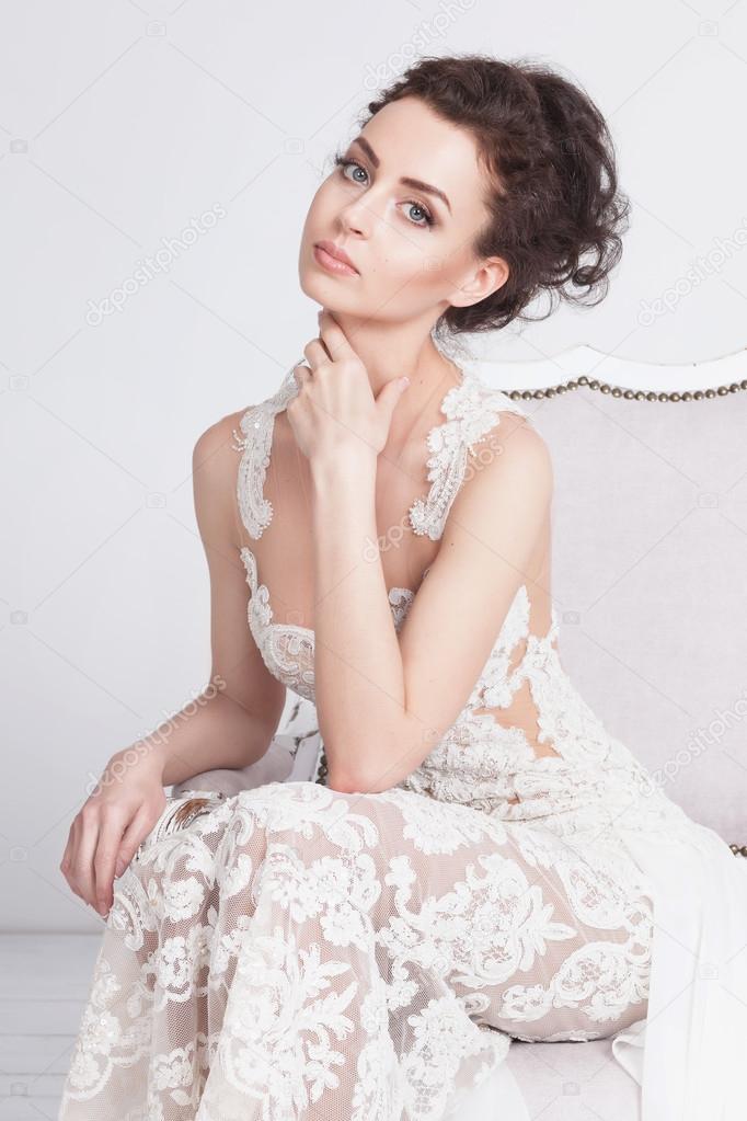 3c02cecc8a68e0 Portret van mooie jonge bruid in een luxe kant trouwjurk. Ze zit op een  witte vintage sofa. Ze is een elegante en slanke