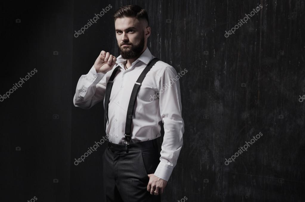 Attractive Bearded Man In A White Shirt And Suspenders Standing Near