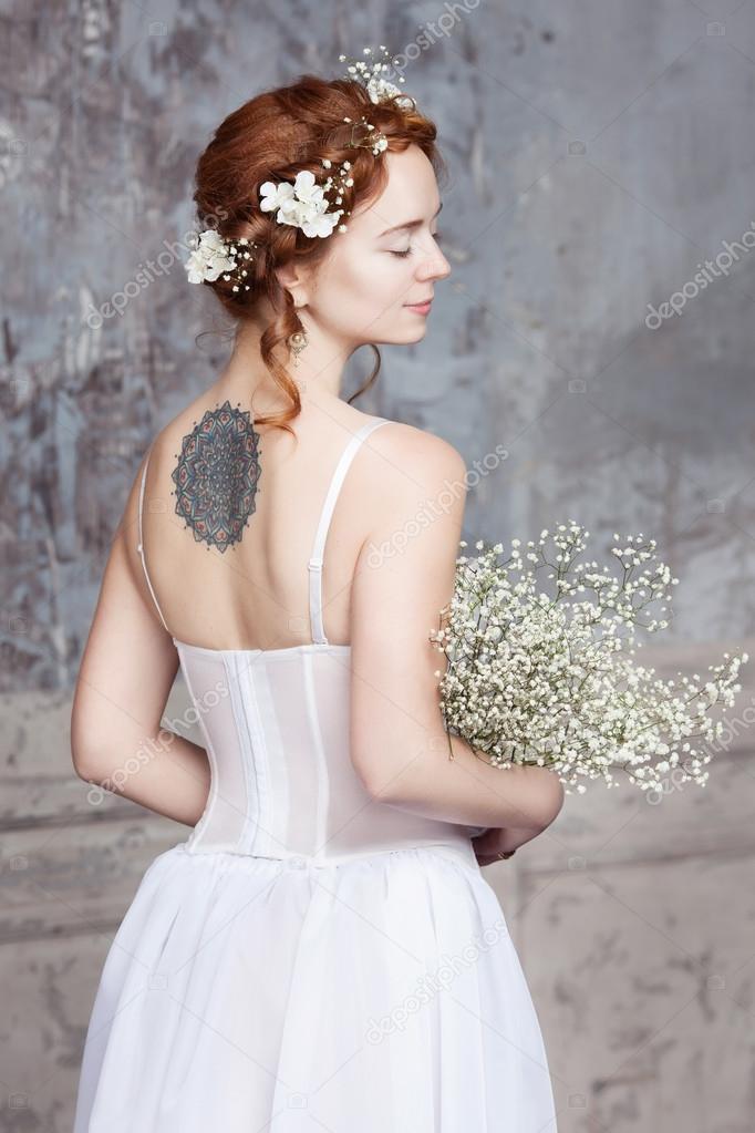 joven pelirroja novia en vestido de boda elegante. ella está con la
