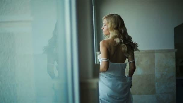 Sexy blonďatá nevěsta dívat stranou na bílé roucho krátké zadní pohled