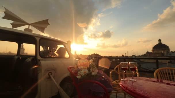 Mladí, milující, pár líbání v veteránem na střešní kavárnu s sklenice červeného vína a květiny na stole. Pohled na starověké město stavební a zároveň pršet. Romantický západ slunce na pozadí