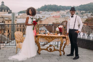 Charming african wedding couple stands on the balcony near the oriental-style wedding table