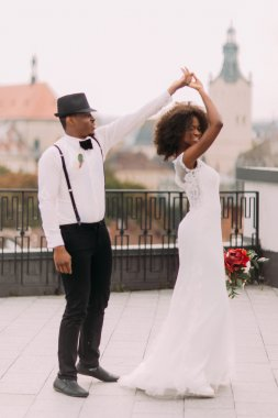 African wedding couple gracefully dancing on the rooftop
