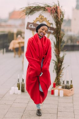 Stylish black girl  in red plaid cheerfully smiling on the rooftop