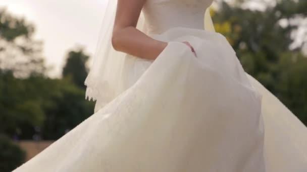 bella novia en danzas de vestido de encaje blanco en los campos