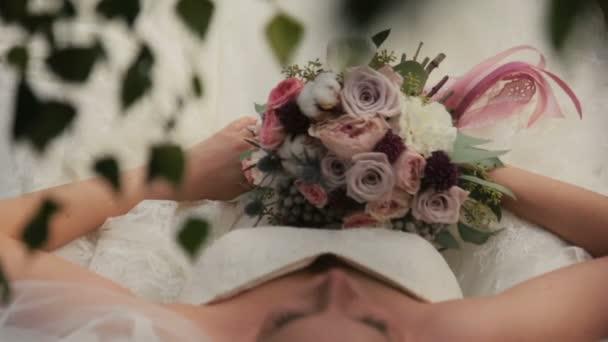 Krásná nevěsta, ležící na lodi s kyticí v ruce