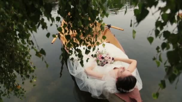 Charming brunette bride lying in the canoe with bouquet in hands. Honeymoon in Paris, France.