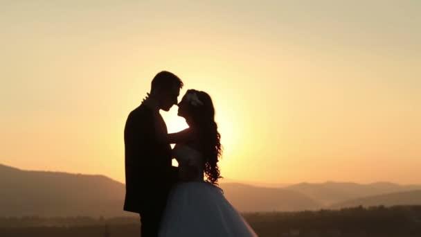 Krásné svatební pár políbit na západ slunce v horách