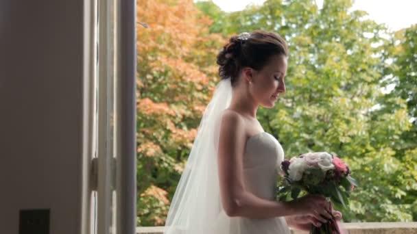 Krásná bruneta nevěstu, Svatební kytice, stojící u okna