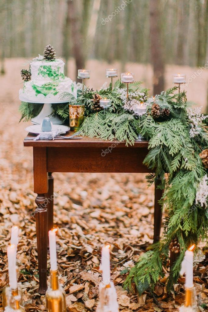 Vintage table with cake and candles in the autumn forest
