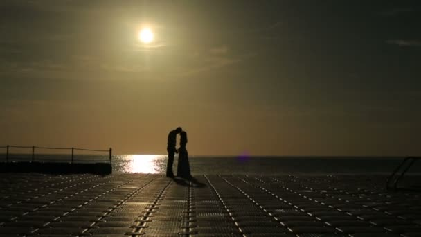 Silhouettes of romantic wedding couple kissing on yacht. Sunset backgound. Honeymoon in Egypt