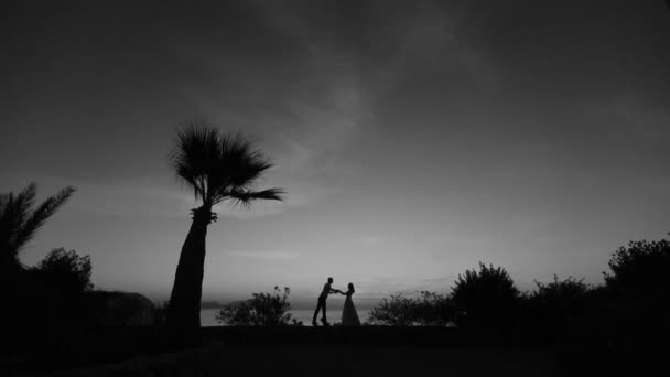 Silhouettes of wonderful couple holding hands and kissing. Romantic sunset on background. Black and white
